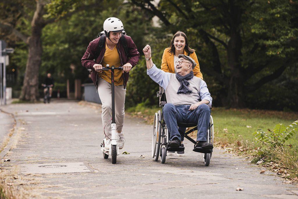 Senior man in wheelchair having fun with his adult grandchildren outdoors